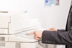 Mann, der eine Kopienmaschine (flachen, verwendet DOF) Stockbild