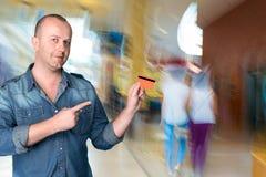 Mann, der eine Kreditkarte in seiner Hand hält Lizenzfreies Stockfoto