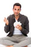 Mann, der eine Münze in ein Sparschwein einsetzt Stockbild