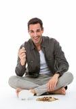 Mann, der eine Münze lächelt und hält Lizenzfreie Stockfotografie