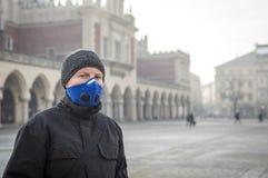 Mann, der eine Maske - Schutz gegen Smog verwendet lizenzfreie stockfotografie