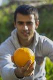 Mann, der eine Orange hält Lizenzfreie Stockbilder