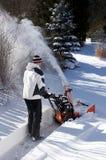 Mann, der eine Schneefräse verwendet Lizenzfreie Stockfotos