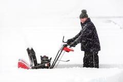 Mann, der eine Schneekanone verwendet Stockbild