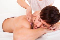 Mann, der eine Schultermassage hat stockfotografie