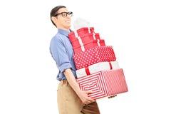 Mann, der eine schwere Last von Geschenken trägt Stockbilder