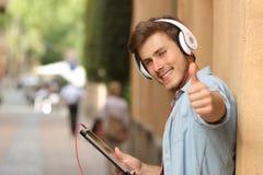 Mann, der eine Tablette mit den Daumen oben in der Straße verwendet Stockbilder