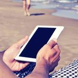 Mann, der eine Tablette oder ein eBook auf dem Strand, mit einem Retro- Effekt verwendet Lizenzfreies Stockbild