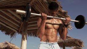 Mann, der eine Trainings-Übung mit Barbell auf einem Strand tut stock footage