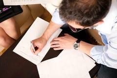 Mann, der eine Vereinbarung unterzeichnet Stockbilder