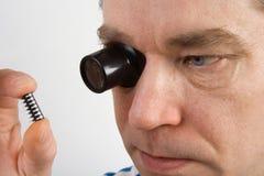 Mann, der eine Vergrößerungslupe verwendet stockfotos