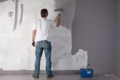Mann, der eine Wand malt. Stockfotos