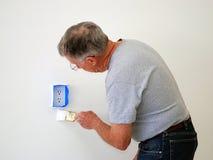 Mann, der eine Wand malt Stockfotos
