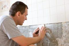 Mann, der eine Wand mit Ziegeln deckt Stockfoto