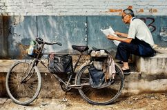 Mann, der eine Zeitung nahe bei seinem Fahrrad in einem typischen Stadt hutong liest stockfotos