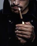 Mann, der eine Zigarette beleuchtet Stockfotos