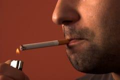Mann, der eine Zigarette beleuchtet stockfotografie