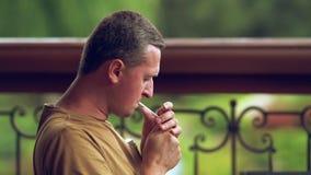 Mann, der eine Zigarette draußen rauchend sitzt stock video