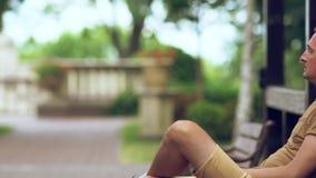 Mann, der eine Zigarette in einem Park rauchend sitzt stock video