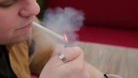 Mann, der eine Zigarette am Tisch raucht stock video footage