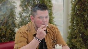 Mann, der eine Zigarette am Tisch raucht stock footage