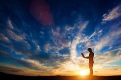 Mann, der an einem Laptop bei Sonnenuntergang arbeitet Lizenzfreies Stockbild