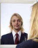 Mann, der in einem Spiegel schaut Stockbild