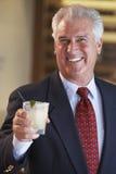 Mann, der an einem Stab etwas trinkt Lizenzfreies Stockfoto