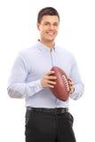 Mann, der einen amerikanischen Fußball und eine Aufstellung hält Stockfotos