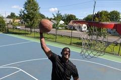 Mann, der einen Basketball eintaucht Stockfotografie