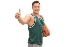 Mann, der einen Basketball hält Stockfoto