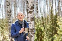 Mann, der einen Becher im Wald hält Stockfotos