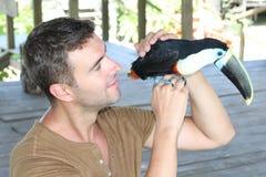 Mann, der einen bunten Tukanvogel streichelt stockfoto