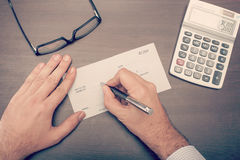Mann, der einen Check schreibt Lizenzfreies Stockfoto