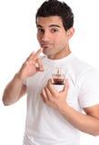 Mann, der einen Duftstoff fördernd sich empfiehlt Stockfotos