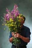 Mann, der einen enormen Blumenstrauß hält Lizenzfreie Stockbilder