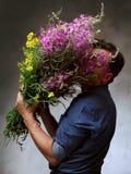 Mann, der einen enormen Blumenstrauß hält Stockbild