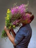 Mann, der einen enormen Blumenstrauß hält Lizenzfreies Stockfoto
