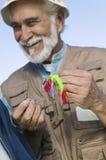 Mann, der einen Fliegen-Fischen-Köder bindet Lizenzfreie Stockbilder
