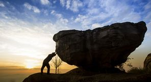 Mann, der einen Flussstein auf einem Felsen drückt Lizenzfreie Stockbilder