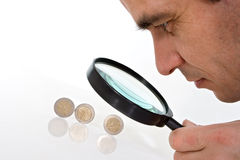 Mann, der einen genauen Blick auf Euromünzen hat Lizenzfreie Stockfotos