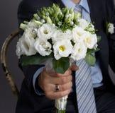 Mann, der einen Hochzeitsblumenstrauß anhält Lizenzfreies Stockfoto