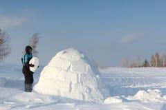 Mann, der einen Iglu in einem Blizzard errichtet Lizenzfreie Stockfotos