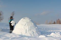 Mann, der einen Iglu in einem Blizzard errichtet Stockbild