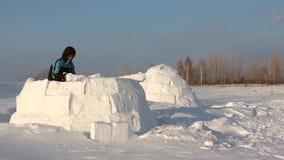 Mann, der einen Iglu im Winter errichtet stock video