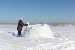 Mann, der einen Iglu von Schneeblöcken auf einer Lichtung errichtet Stockbilder