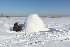 Mann, der einen Iglu von Schneeblöcken auf einer Lichtung errichtet Lizenzfreie Stockfotos