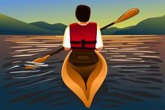 Mann, der einen Kajak im See reitet Lizenzfreie Stockfotos