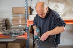 Mann, der einen klaren Acrylrahmen bohrt Lizenzfreie Stockbilder