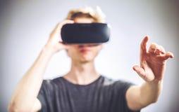 Mann, der einen Kopfhörer der virtuellen Realität verwendet Stockbild